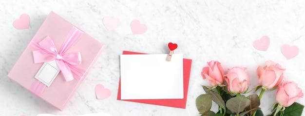 Fondo di concetto di progetto di san valentino con il fiore della rosa rosa e la scatola regalo su fondo bianco di marmo