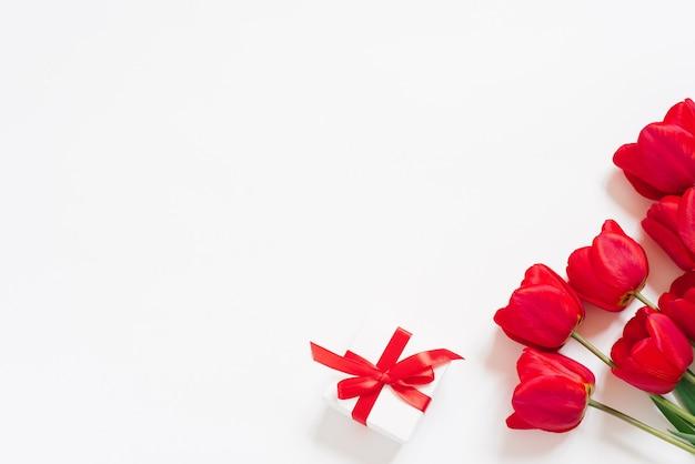 Piatto di san valentino. tulipani rossi e confezione regalo con fiocco rosso su sfondo bianco con spazio di copia.