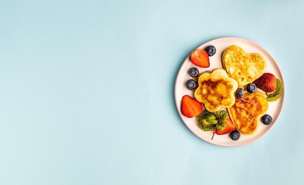 Il piatto di san valentino giaceva con frittelle a forma di cuore su un blu.