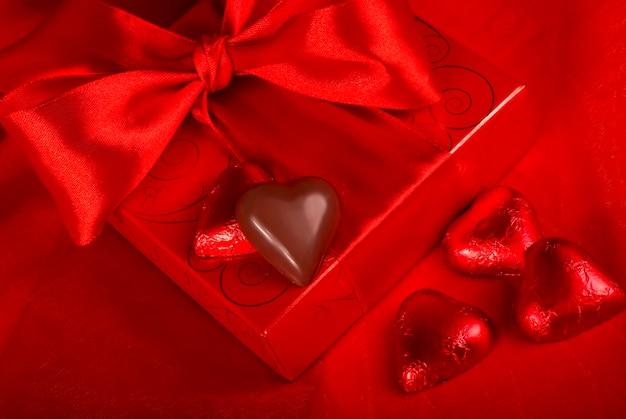 San valentino. confezione regalo e caramelle a forma di cuore su fondo rosso