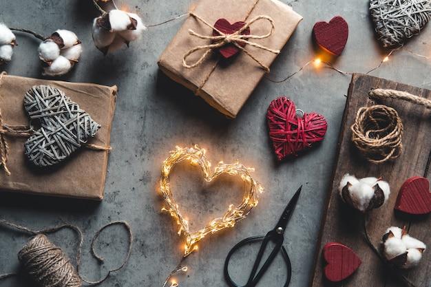 San valentino, confezione regalo di carta kraft. confezionamento e preparazione di regali per la festa. romanticismo, appuntamento, amore