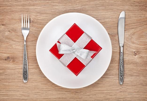 Confezione regalo di san valentino su piatto e posate. vista dall'alto sullo sfondo del tavolo in legno