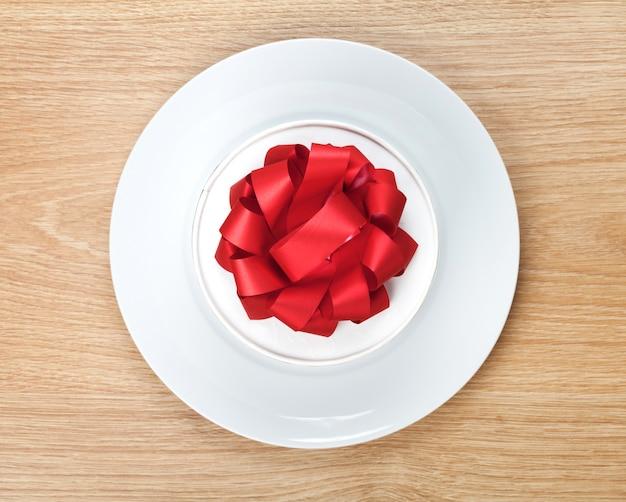 Confezione regalo di san valentino sul piatto. vista dall'alto sullo sfondo del tavolo in legno