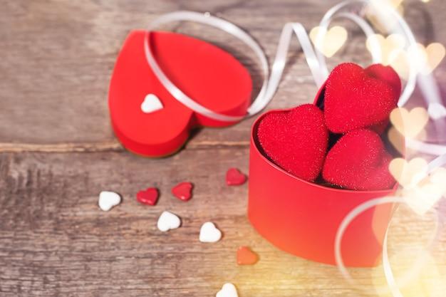 Confezione regalo di san valentino con cuori rossi, caramelle e nastri. scatola a forma di cuore decorata con caramelle e nastri su fondo in legno