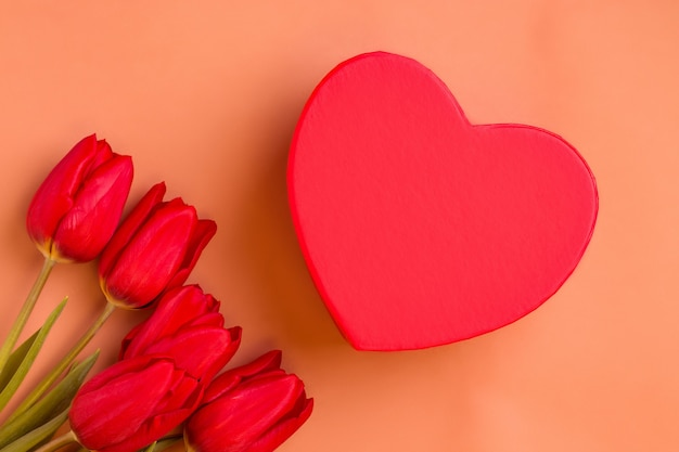 Regalo di san valentino. tulipani rossi con scatola a forma di cuore su sfondo marrone