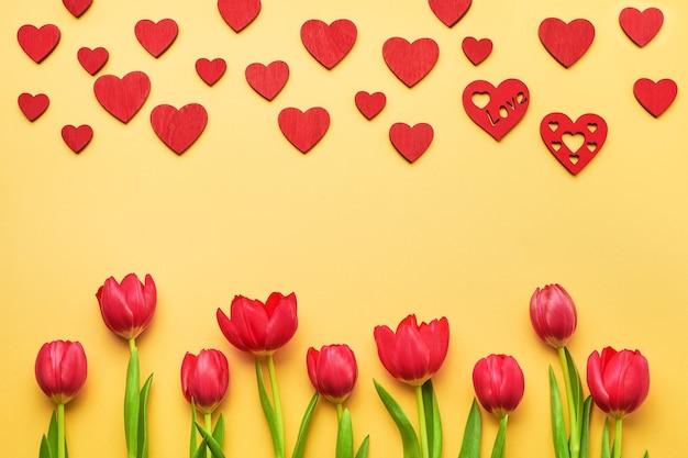 Biglietto di auguri di san valentino. bouquet di tulipani rossi e cuori rossi su fondo giallo. copia spazio, piatto laici