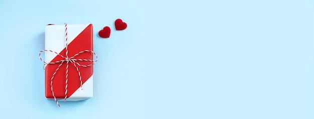 Concetto di design regalo fatto a mano di auguri di san valentino - vista dall'alto della confezione regalo avvolta su sfondo blu brillante, layout sopraelevato piatto.