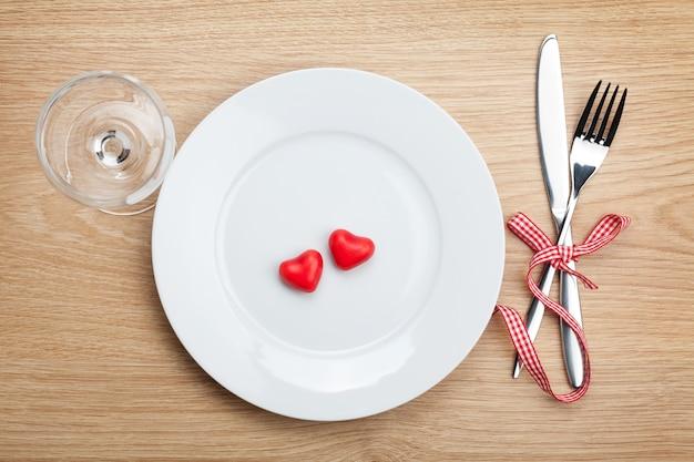 Caramella a forma di cuore di san valentino sul piatto con posate e bicchiere di vino. sullo sfondo del tavolo in legno