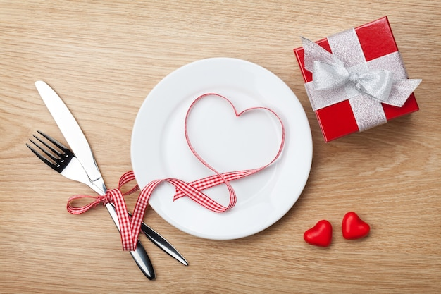 Nastro rosso a forma di cuore di san valentino sul piatto con argenteria e confezione regalo. sullo sfondo del tavolo in legno