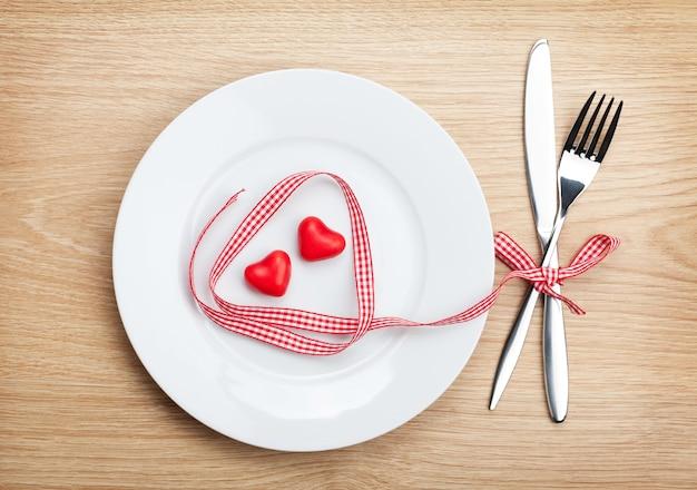 Nastro rosso a forma di cuore di san valentino sul piatto con posate. sullo sfondo del tavolo in legno