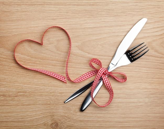 Nastro rosso e argenteria a forma di cuore di san valentino. sullo sfondo del tavolo in legno
