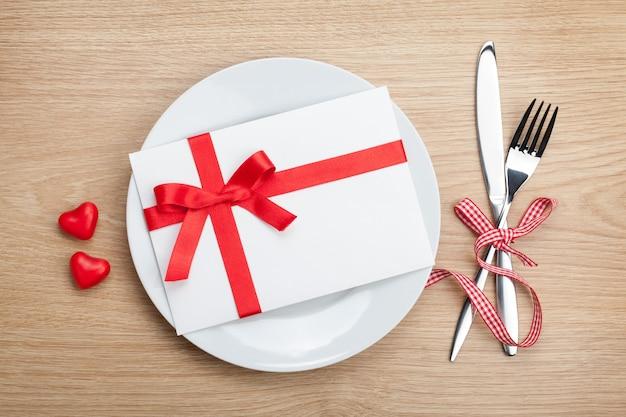Lettera d'amore di san valentino sul piatto con posate. sullo sfondo del tavolo in legno