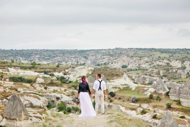 La coppia di innamorati di san valentino nella natura si abbraccia e si bacia, l'uomo e la donna si amano. montagne della cappadocia in turchia bella coppia festeggia san valentino, coppia di innamorati sullo sfondo delle montagne