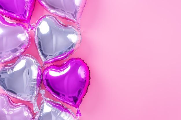 Concetto di design minimale di san valentino - palloncino in lamina a forma di bel cuore reale isolato su sfondo rosa pallido