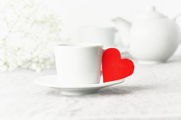 San valentino. colazione del mattino per due persone con tè e fiori. il cuore in feltro rosso è il simbolo degli innamorati
