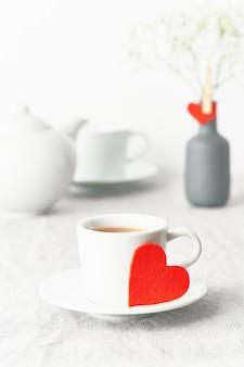 San valentino. colazione del mattino per due persone con tè e fiori. cuore di feltro rosso