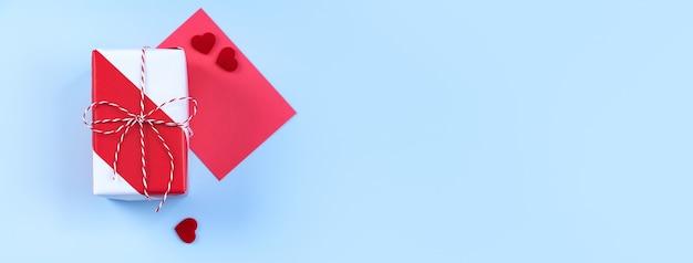 San valentino, concetto di design artistico per la festa della mamma per la promozione - confezione regalo incartata rossa e bianca isolata su sfondo di colore azzurro pastello, disposizione piatta, vista dall'alto.