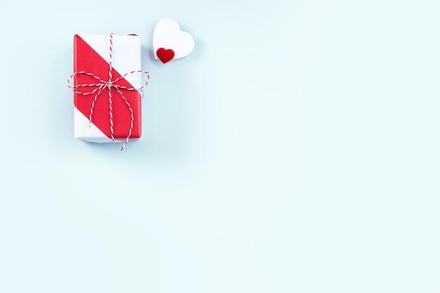 San valentino, concetto di design regalo fatto a mano per la festa della mamma - confezione regalo avvolta isolata su sfondo di colore azzurro pastello, disposizione piatta, vista dall'alto. Foto Premium