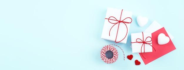 San valentino, concetto di design regalo fatto a mano per la festa della mamma - confezione regalo avvolta isolata su sfondo di colore azzurro pastello, disposizione piatta, vista dall'alto.