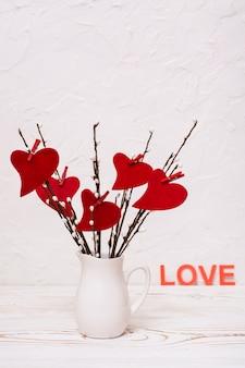 San valentino. cuori di feltro rosso su rami di salice in una brocca bianca sul tavolo
