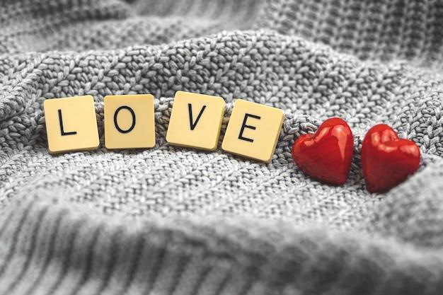 Concetto di cuori rossi di san valentino, composizione di cubi con parola amore, coppia, biglietto di auguri, macro copia spazio foto