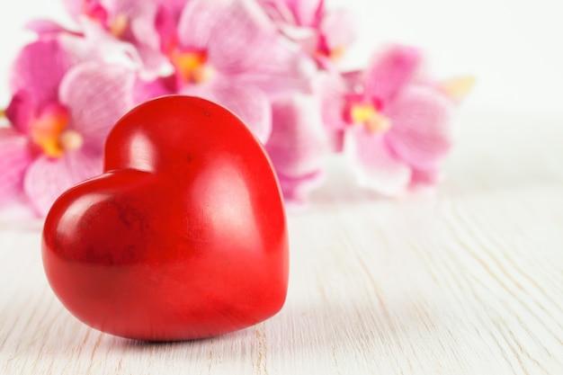 Cuore rosso di forma di san valentino e fiori di orchidea rosa su fondo di legno bianco con spazio vuoto per testo.