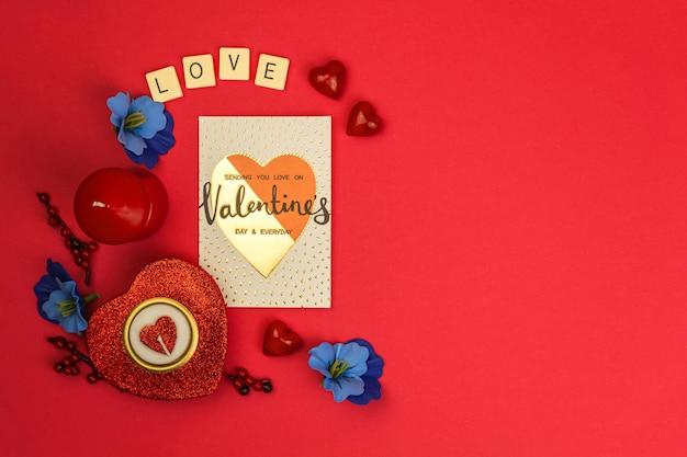 Concetto romantico di san valentino con cuori rossi su sfondo rosso, fiori, candele, parola amore, biglietto di auguri, vista dall'alto, copia spazio foto