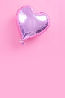 Concetto di design romantico di san valentino - bellissimo palloncino in lamina a forma di cuore reale isolato su sfondo rosa pallido, vista dall'alto, piatto, sopra la fotografia.