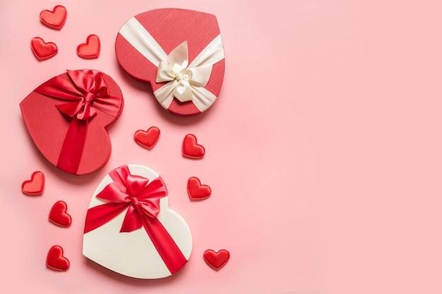 Regali romantici di san valentino con cuori rossi su sfondo rosa. lay piatto. biglietto di auguri con copia spazio.