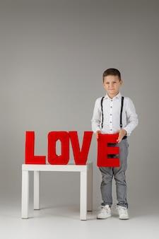 San valentino. ragazzo bambino alla moda che tiene le lettere rosse di parola amore su fondo grigio