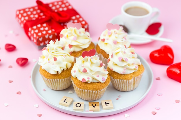 Dolci di san valentino. cupcakes decorati con cuori, confezione regalo e tazza di caffè