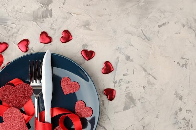 Impostazione della tabella di san valentino piatto blu con un coltello e forchetta e cuori rossi su uno sfondo di cemento chiaro.