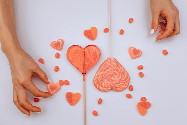 San valentino. vista dall'alto. le mani della ragazza spostano le caramelle a forma di cuori su uno sfondo bianco