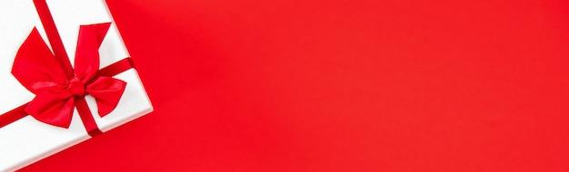 Contenitore di regalo di nozze o di san valentino sul fondo rosso dell'insegna