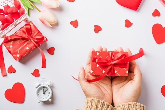 San valentino. la donna passa il regalo o la presente scatola decorata e sorpresa del cuore rosso