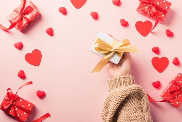San valentino. la donna passa il regalo o la presente scatola decorata