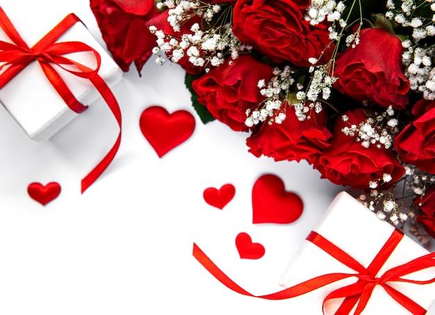 Scatole regalo di san valentino e bouquet di rose rosse su una superficie bianca