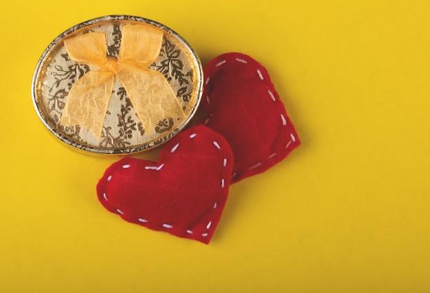 Regalo di san valentino con cuori rossi su sfondo giallo.