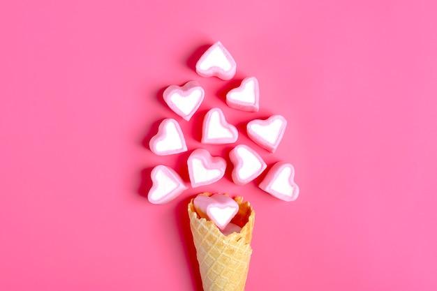 Cartolina di san valentino - marshmallow a forma di un cuore e cono gelato su sfondo rosa