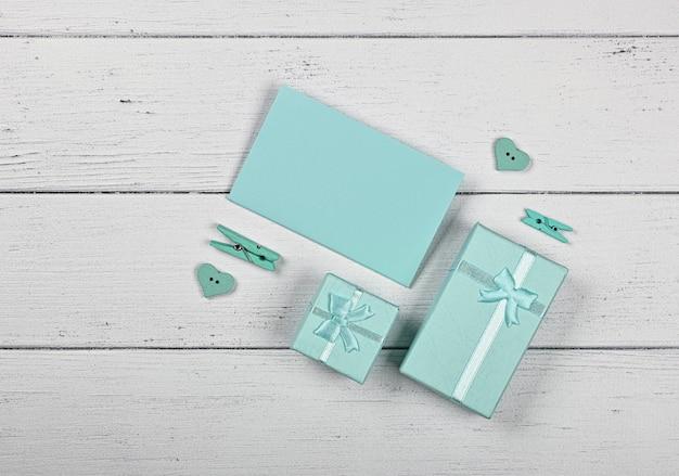 Modello di san valentino di scatole regalo di colore menta verde acqua con fiocchi di nastro in chiffon e nota di carta su sfondo bianco tavolo in legno, primo piano laici, vista dall'alto in alto, direttamente sopra