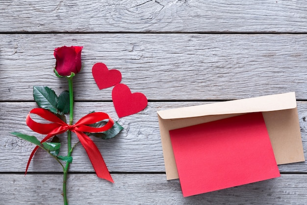 San valentino con fiore rosa rosso e cuori di carta fatta a mano e biglietto di auguri in busta su legno rustico