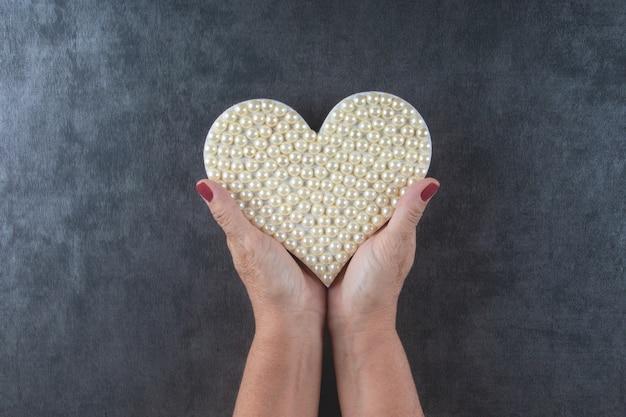 Sfondo di san valentino con mano che tiene il cuore con perle bianche.