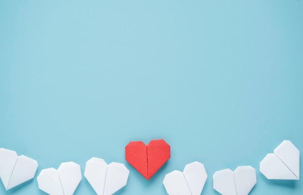 Concetto di san valentino, cuore rosso e bianco su sfondo blu.