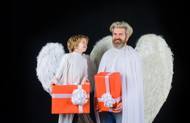 Angeli di san valentino con confezione regalo padre felice in costume da angelo con figlio piccolo che l'angelo tiene presente