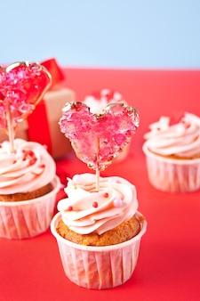 San valentino cupcake glassa di formaggio cremoso decorato con lecca-lecca caramelle cuore e confezione regalo sullo sfondo.