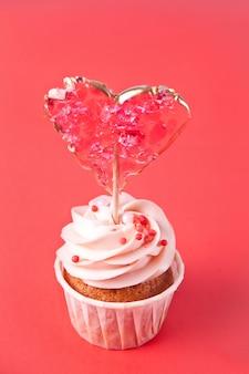 San valentino cupcake glassa di formaggio cremoso decorato con lecca-lecca caramelle cuore su rosso