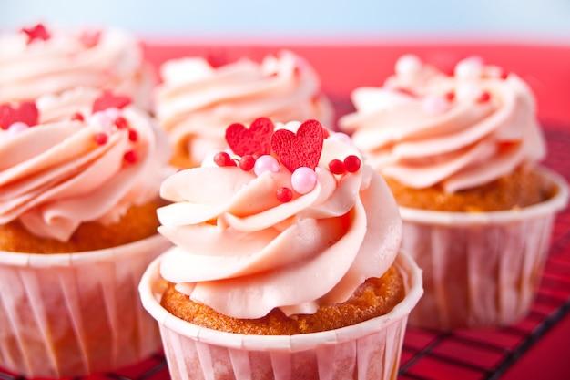 Glassa di crema di formaggio cupcakes di san valentino decorata con caramelle di cuore