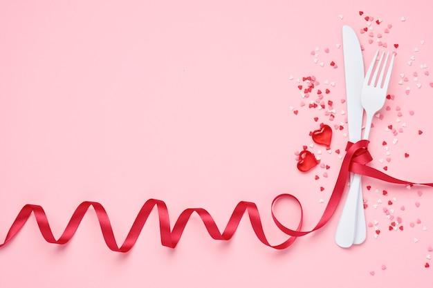 San valentino sfondo o concetto per il menu del pranzo. posate bianche, forchetta e coltello intrecciate con nastro rosso e piccoli cuori