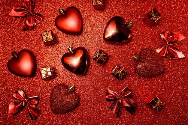 Sfondo di san valentino, cuori rossi e regali su rosso lucido