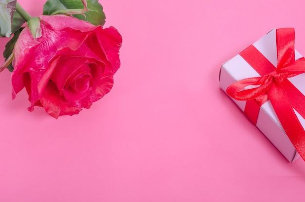 Sfondo di san valentino. rosa rossa con un regalo bianco su uno sfondo rosa con spazio di copia.